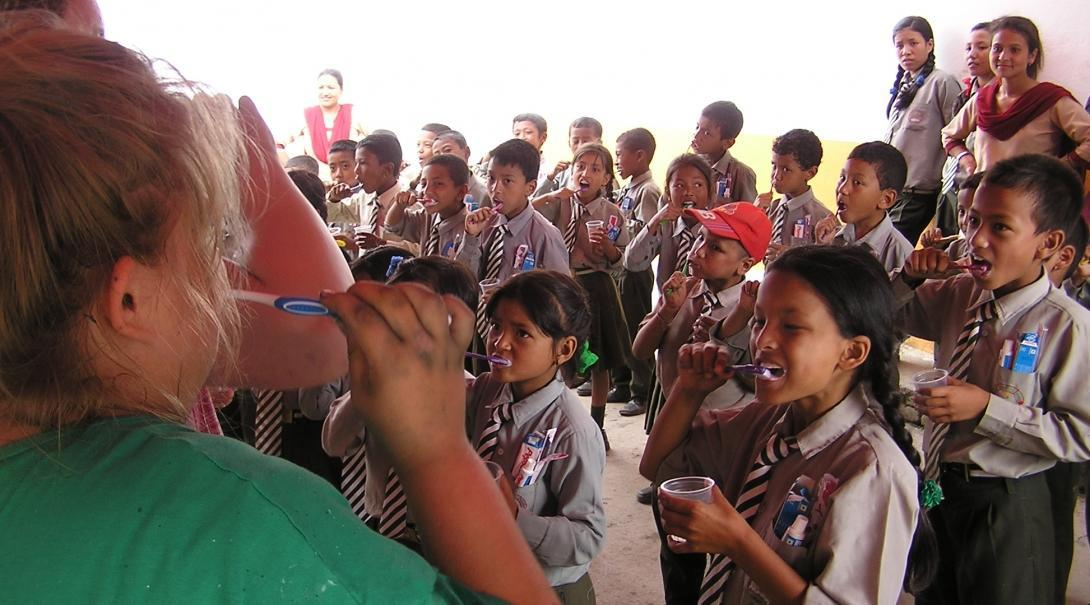Pasante de Odontología enseñando a unos niños a cepillarse correctamente los dientes.